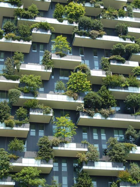 Bloque de viviendas moderno con amplios balcones repletos de arbustos y plantas