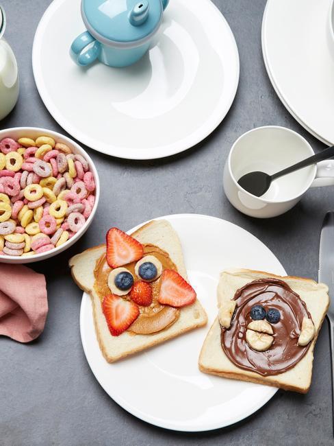 Szary stół kuchenny z białymi talerzami i kolorowami tostami oraz miską płatków śniadaniowych