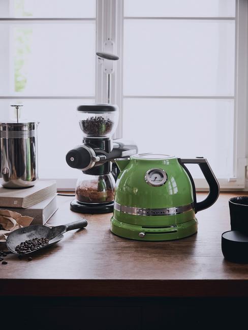 Zielony czajnik stojący na drewninym blacie obok ekspreu na kawę