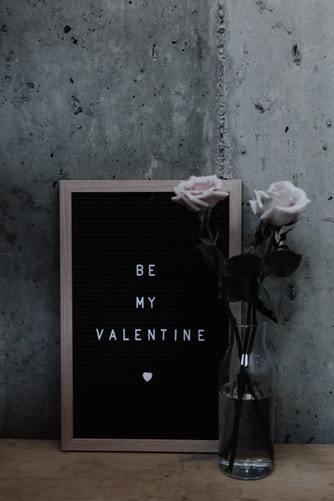 Czarna tablica z napisem oraz wazon z kwiatami stojące przy ścianie