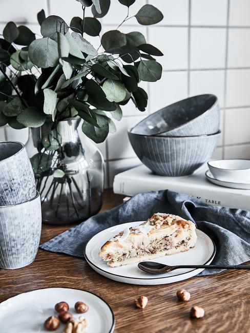 Biała kuchnia z drewnianym blatem na którym leży niebieska zastawa oraz roślina