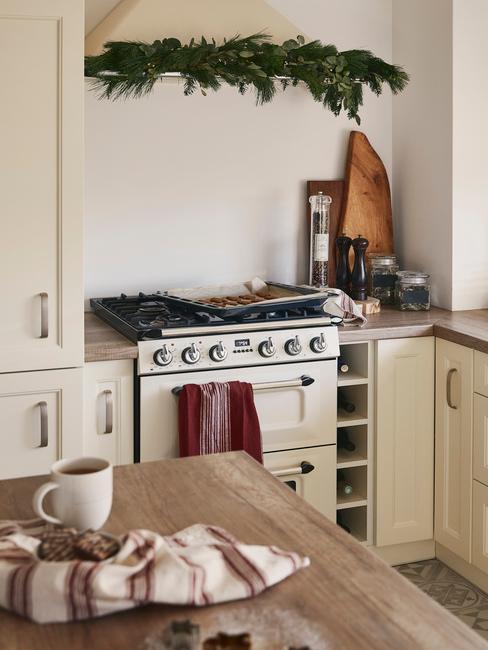Biała kuchnia z drewnianym blatem i beżowymi akcesoriami AGD