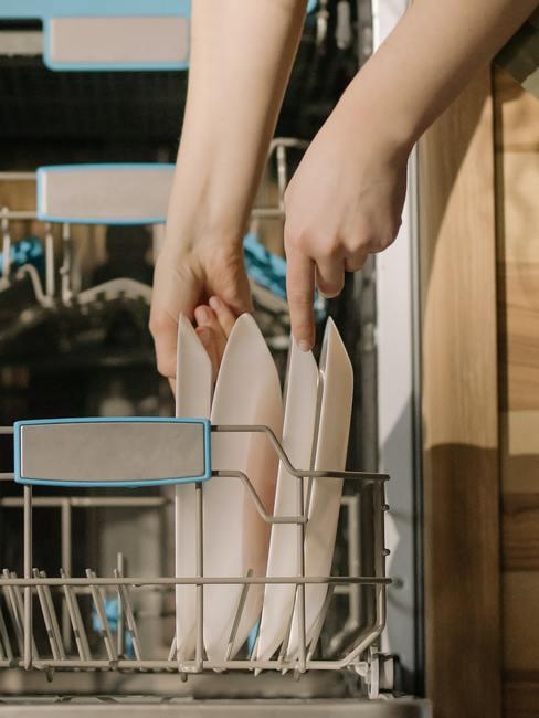 Kobieta wkładająca naczynia do zmywarki