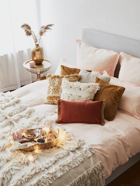 Biała sypialnia z łóżkiem o szarym zagłówku, stolikiem pomocniczym, plecem oraz kolorowymi poduszkami