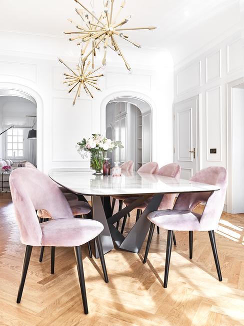 Biała jadalnia ze stołem wykonanym z marmuru i różowymi krzesłami