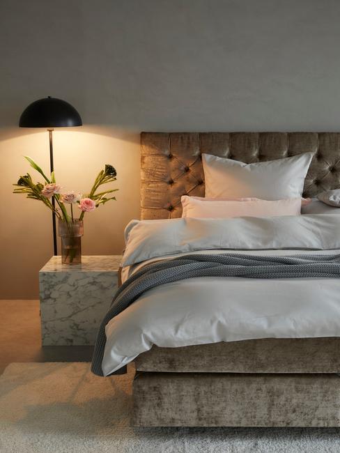 Minimalistyczna sypialnia z łożkiem, czarną lampą oraz marmurowym stolikiem