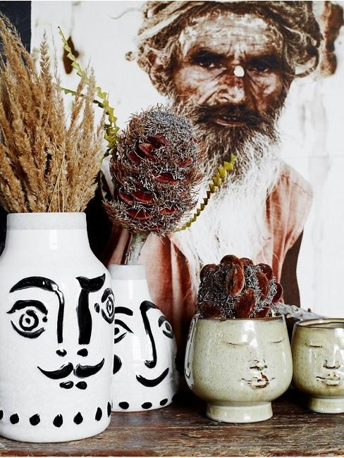Vases with painted faces and dried flowers