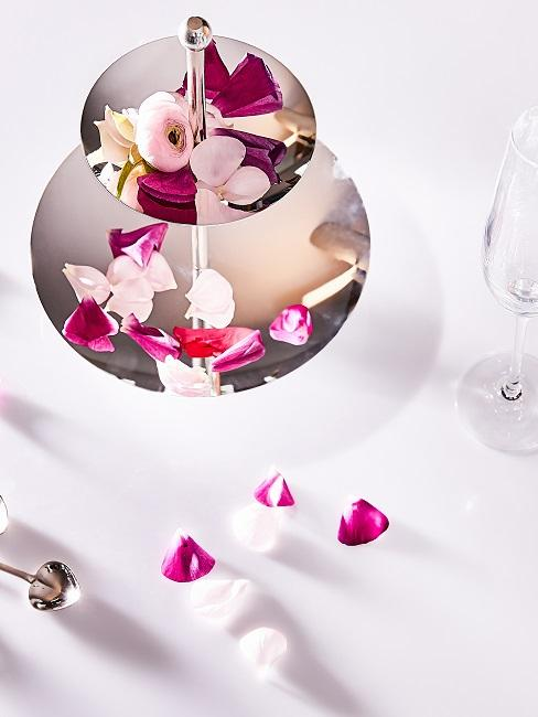 Cake stand as a table decoration with rose petals
