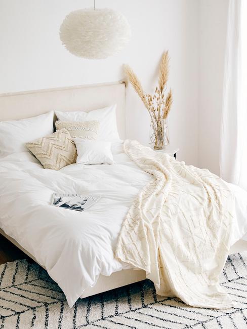 Biała sypialnia z łożkiem na którym znajduje się biała pościel, beżowe poduszki i pled