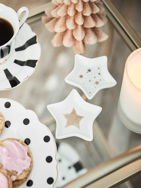 Two small decorative plates in the shape of a star and with a star motif stand on a table next to coffee dishes