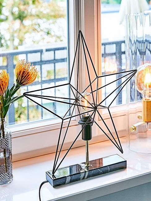 Decorative lamp in star shape on the windowsill in the kitchen