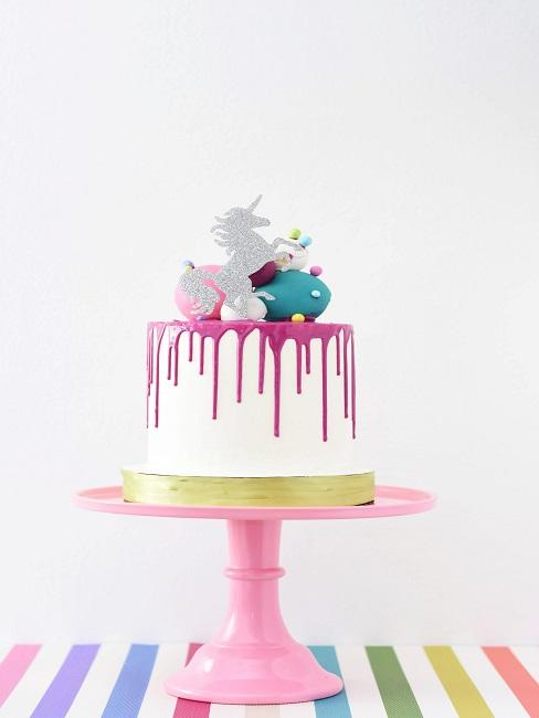 Cake with unicorn decoration on a cake stand in the kitchen
