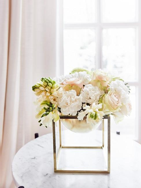 White roses in a golden decorative bowl on a table