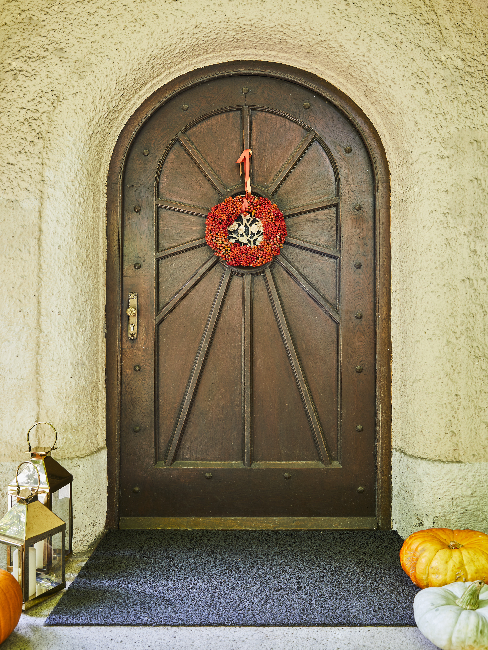 Brown front door with red wreath and lanterns and pumpkins as decoration