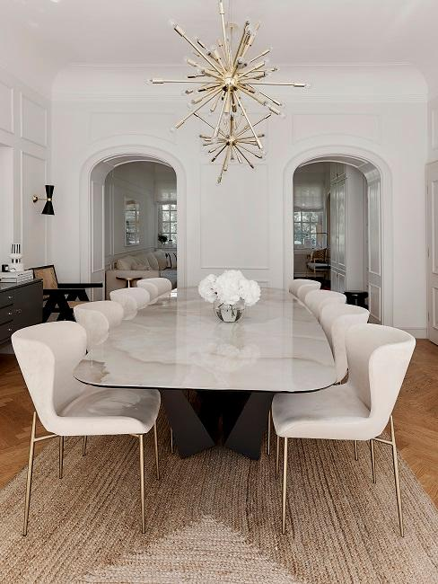 Long dining table with beige chairs and a small vase on the table