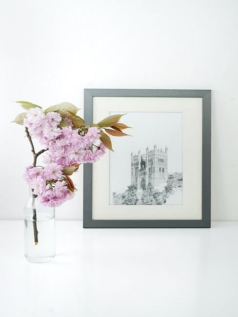 Cherry blossoms in glass vase on chest of drawers next to picture