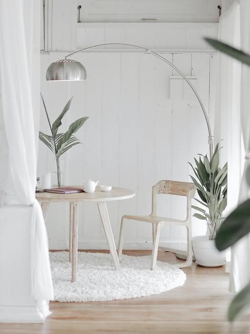 Een kamer in lichte kleuren met een houten tafel en stoel en een metalen lamp, een wit vloerkleed en planten in een modern klassiek interieur