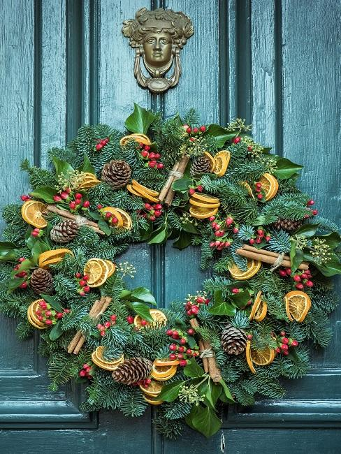 Door wreath with pine cones and dried oranges on a green door