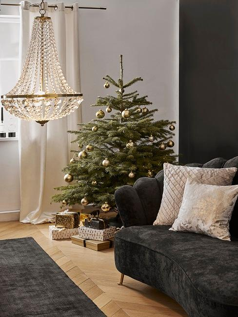 Elegantly decorated fir tree next to dark velvet couch