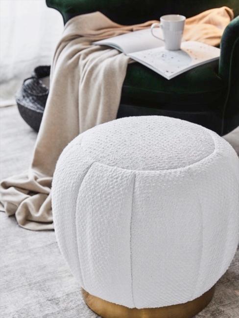 Pouf en tissu bouclé devant un fauteuil en velours bert foncé couvert d'un plaid couleur crème, un livre ouvert posé dessus, sur livre une tasse
