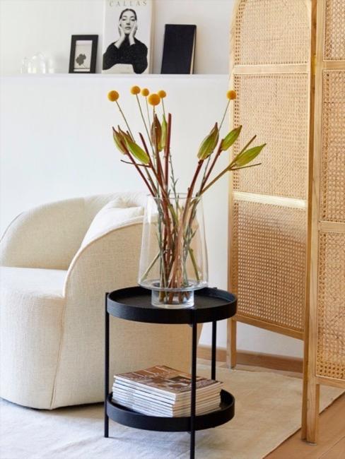 coin séjour avec une petite table d'appoint noire avec un vase rempli des fleurs séchées, un paravent en cannage et un fauteuil clair en tissu bouclé
