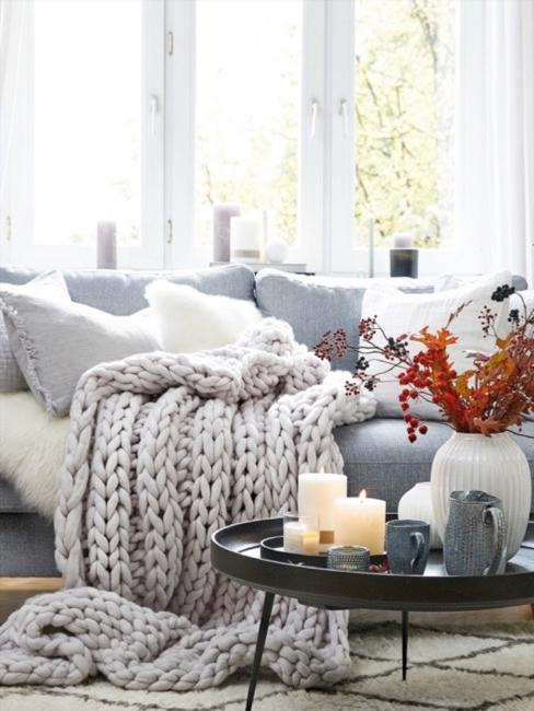 Gruby, przytulny koc na sofie obok udekorowanego stolika kawowego.