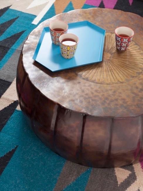 Okrągły, drewniany stolik w stylu etno postawiony na kolorowym dywanie.