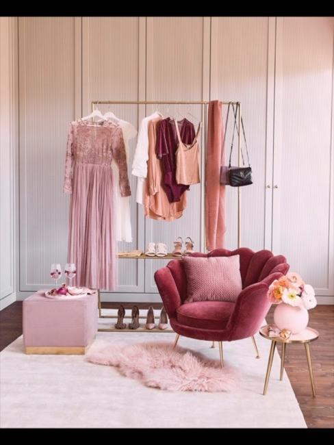 Dywan z różowego sztucznego futra przed wieszakiem z ubraniami obok fotela-muszli
