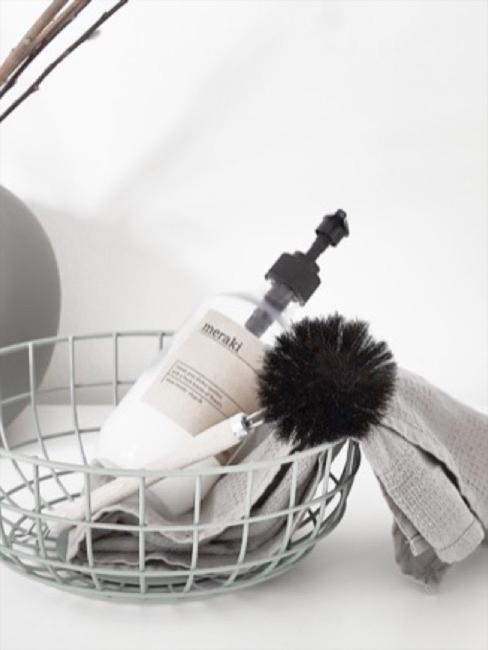 Productos de limpieza sobre cesta en tonos grises