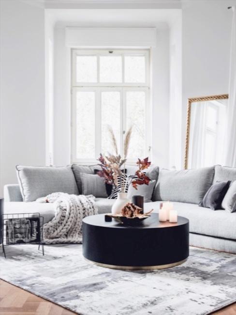 Coin canapé d'un séjour dans les tonalités gris clair, avec canapé et table basse noire, herbe de la pampa dans un vase trône sur la table