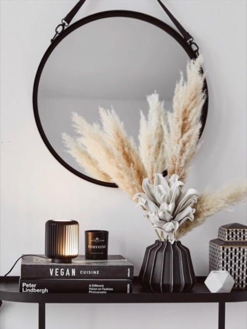 L'herbe de la pampa claire en vase noir sur buffet noir avec livres déco et miroir mural rond.