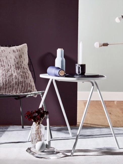 Pokój ze ścianą w kolorze fioletowym przed którą stoi biały stolik z dekoracjami