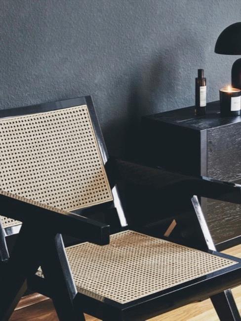 Krzesło z plecionką wiedeńską na ctle ciemnej ściany obok czarnej komody z dekoracjami