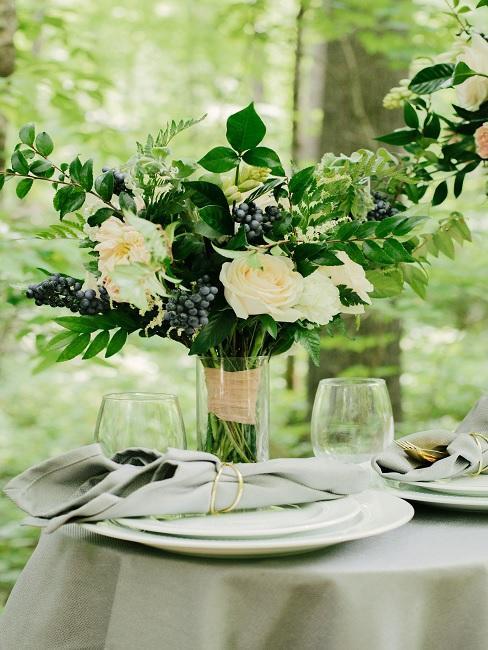 Blumenstrauß mit weißen Rosen und grünen Zweigen auf Hochzeitstafel