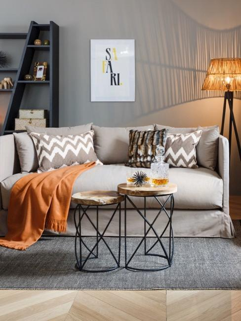 Woonkamer met grijze bank en oranje decoratie