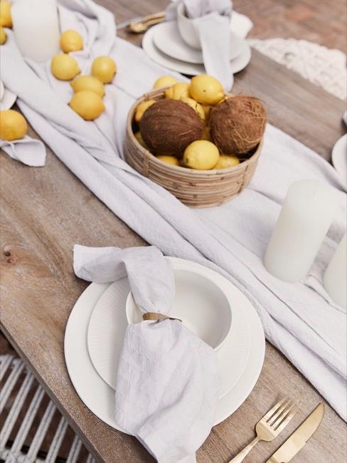 Mesa decorada en blanco con limones y cocos