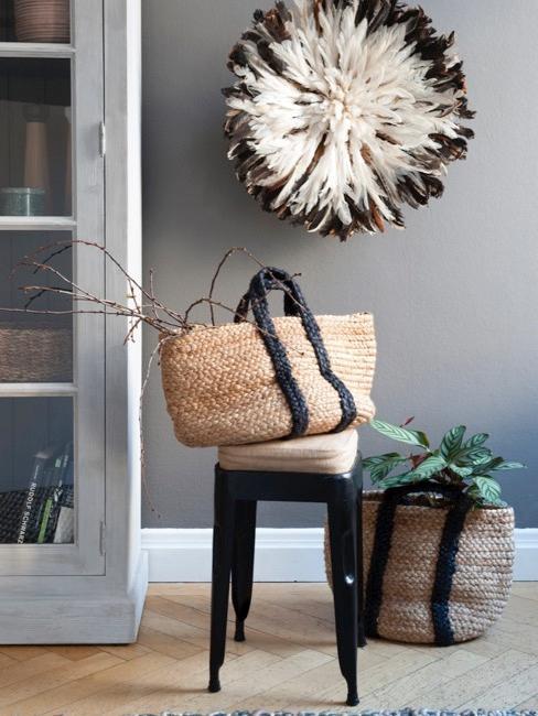 Salón con pared gris oscuro, taburete con cesta de mimbre, mueble de madera grisáceo y plantas