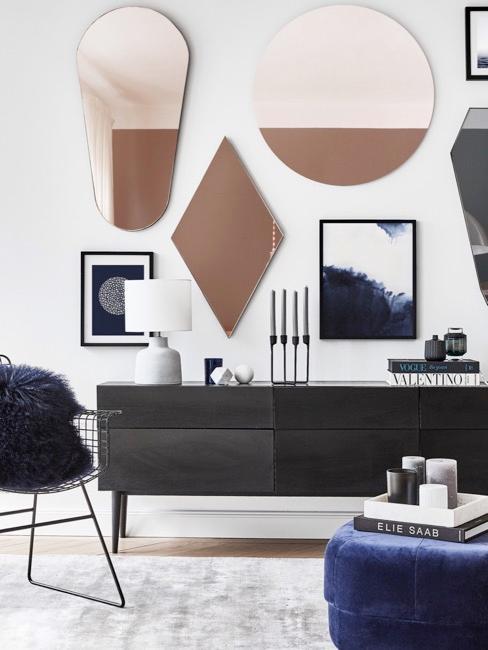 Czarna komoda, powyżej której wiszą liczne różnokształtne lustra i grafiki