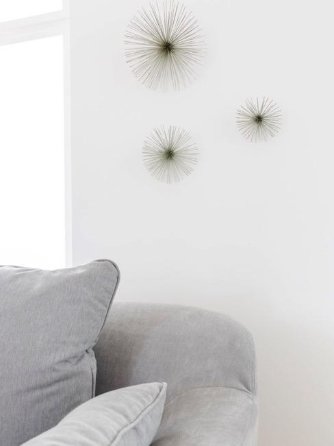 Pared blanca con estrellas plateadas decorativas y sofá gris minimalista
