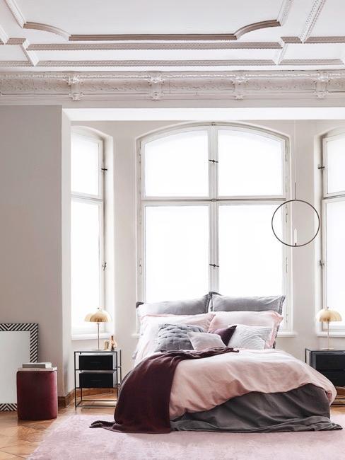 Chambre à coucher rose avec grandes fenêtres blanches et un lit couleur bordeaux et rose