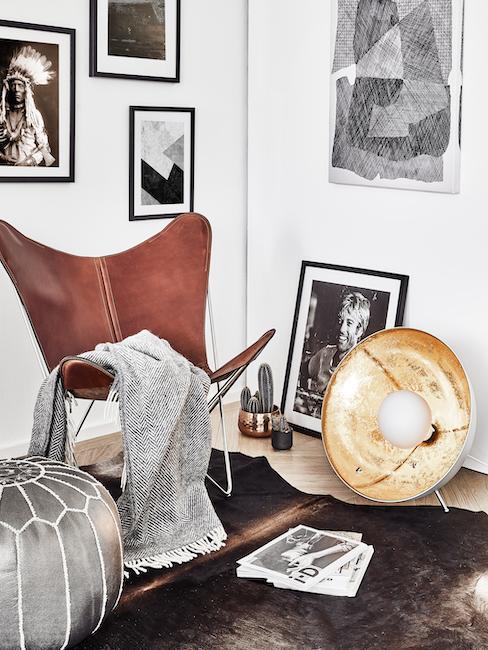 sillón marrón de cuero con una manta de color gris, lámpara reflector y fotos en la pared