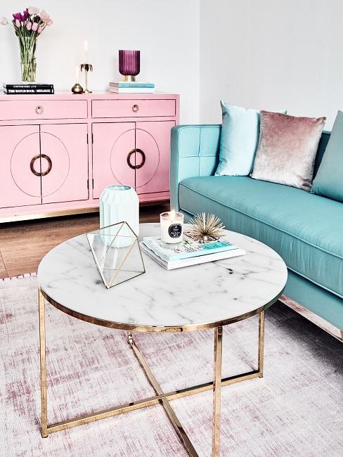 Moderner Couchtisch mit weißer Marmorplatte vor einem grünen Sofa und einem rosafarbenen Sideboard