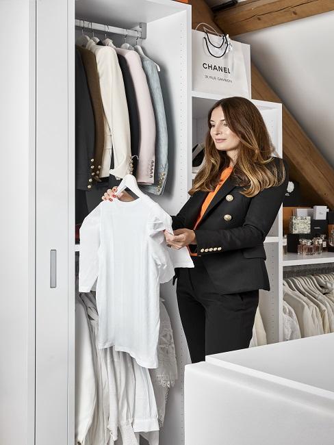 Frau vor offenem Kleiderschrank mit Hemd in der Hand