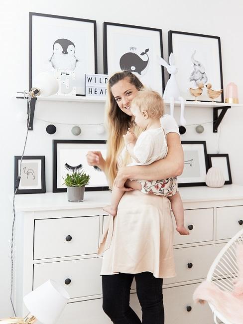 Mutter und Baby vor Kommode mit Bildern als Babyzimmer Deko