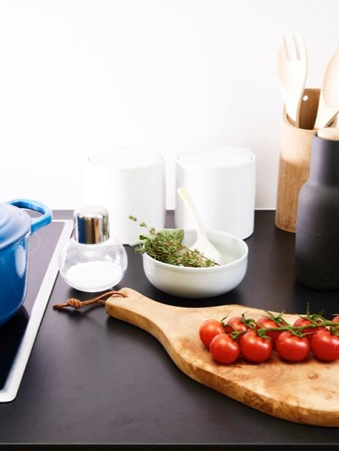 Tabla de cortar con tomates y accesorios de cocina