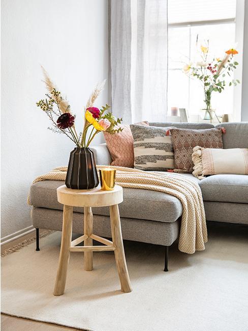 Canapé gris avec divers coussins décoratifs et table d'appoint