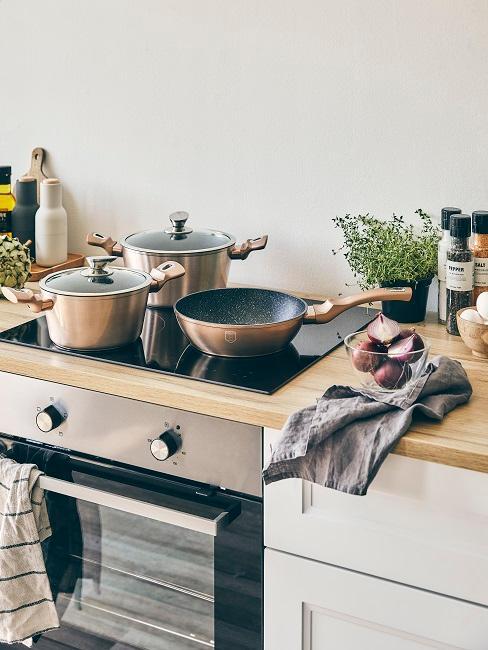 oven en plank, op de kookplaat staan twee potten en een pan en vaatdoeken