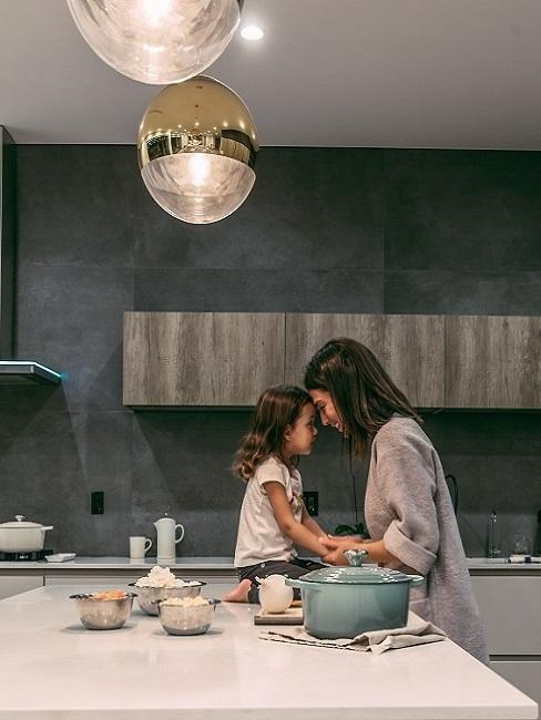 Mutter mit ihrem Kind in der Küche, Stirn an Stirn, das Kind sitzt auf dem Tresen, daneben Küchenzutaten