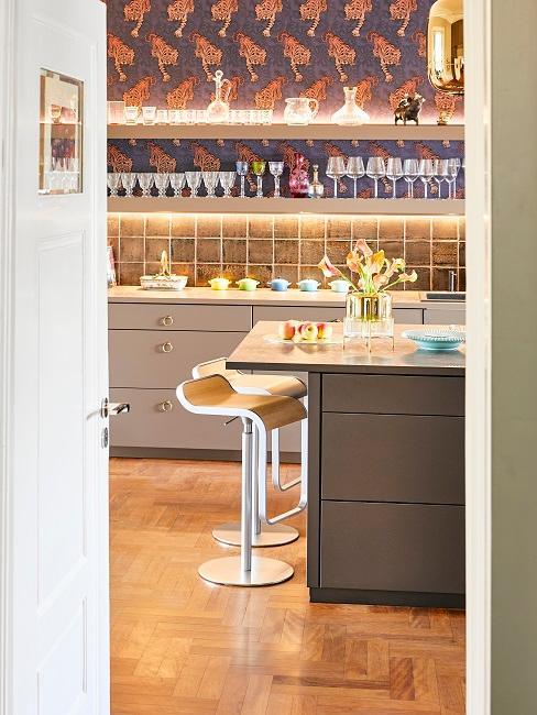 Küche mit Tresen, besonderen Fliesen in Braun und darüber einer Tiger-Tapete