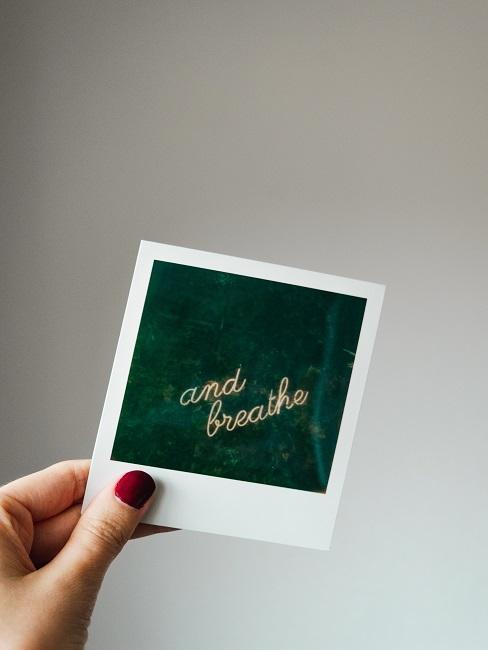 """Polaroid mit """"and breathe"""" Schrift in einer Frauenhand"""